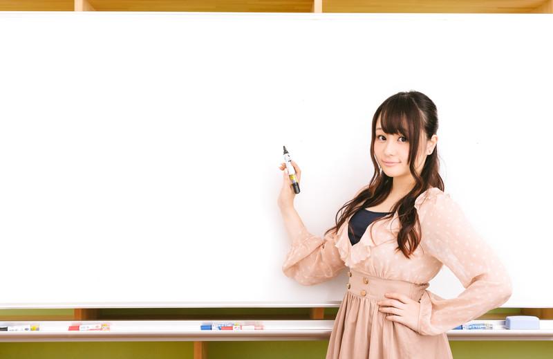 ホワイトボードに書いて説明する美人広報